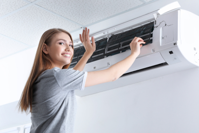 Smiling woman stands next to a wall mounted air conditioning unit