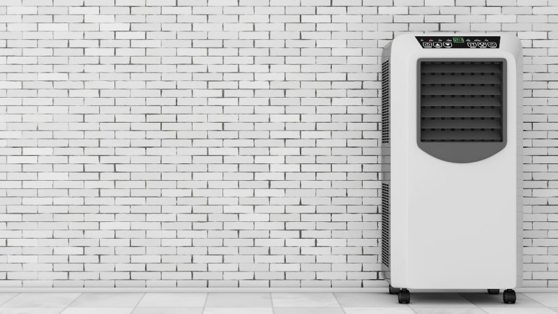 A portable air conditioner stands in front of a brick wall