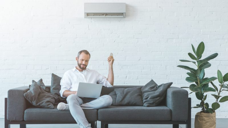 Man adjusts his air conditioning with a remote control while sitting on a sofa