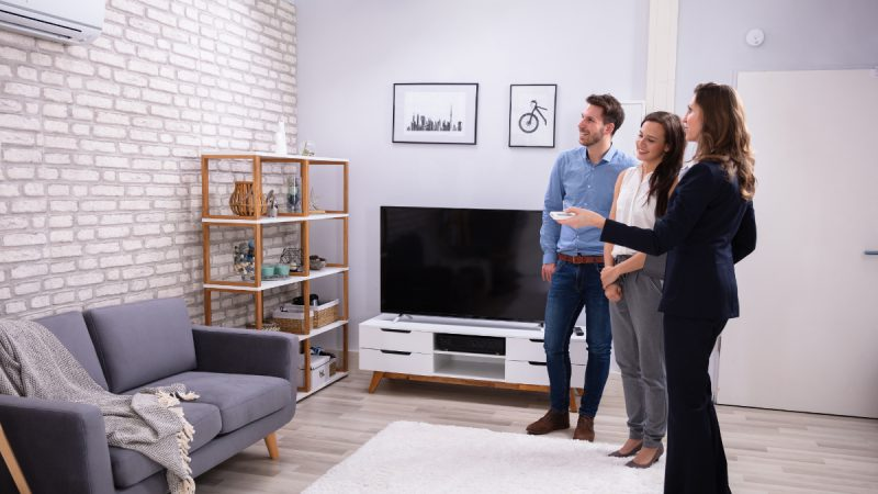Couple and business woman look at split air conditioning system