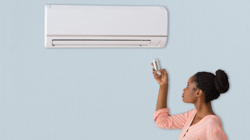 Young woman turns on her R22 refrigerant air conditioning system