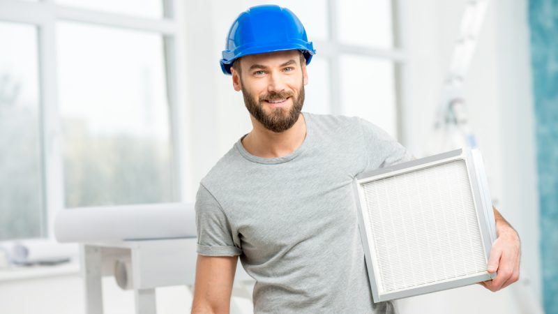 Engineer carries out air conditioning servicing