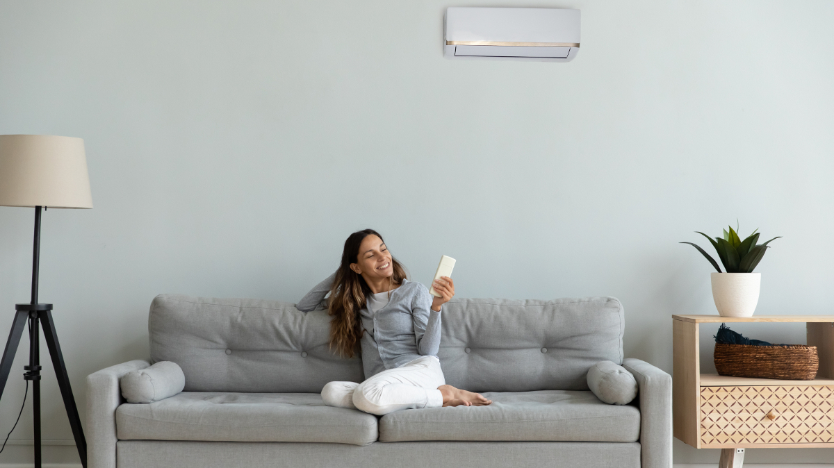 Woman sits on a sofa in a flat and controls her air conditoning