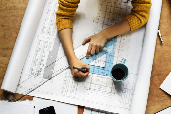 Woman draws on building plans
