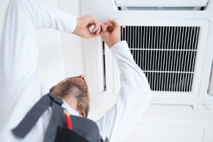 Reliable air conditioning installer works on a ceiling cassette air conditioning unit